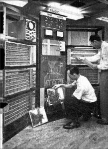 Imagem preto e branco do Tradic, um computador antigo, com vários compartimentos, e dois homens manipulando-o.